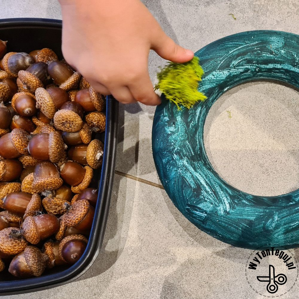 Sticking moss and acorns to the painted polystyrene wreath base